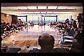 Grande mesa de reunião. Vários homens sentados.