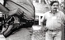 Chico Mendes observa o policial apoiando a mão no revólver