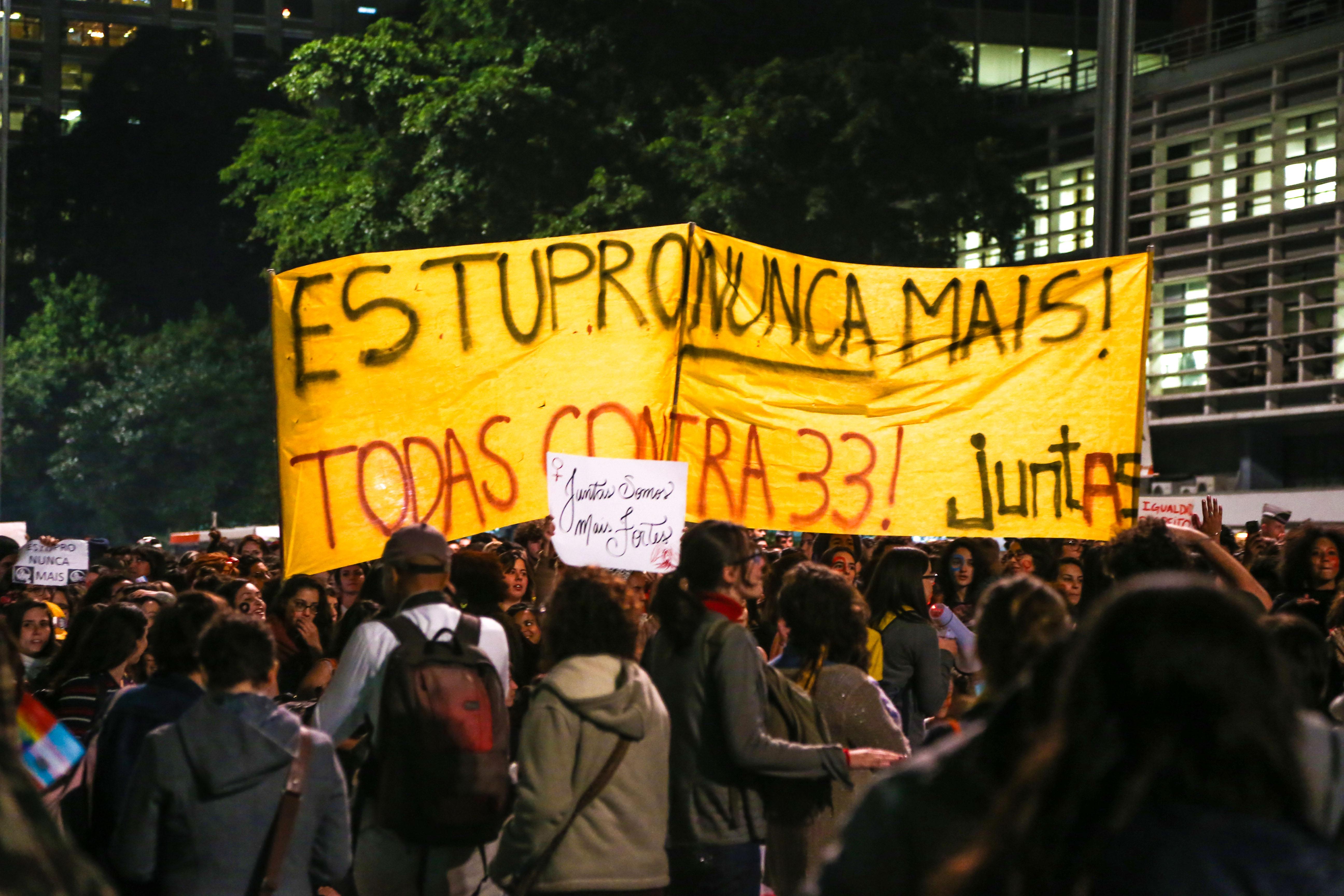 Um grupo de mulheres está reunido numa praça. Elas seguram uma faixa em que se lê: Estupro nunca mais