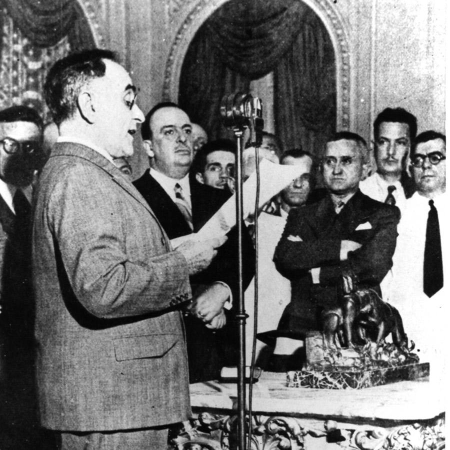 Getúlio Vargas anuncia pelo rádio o início novo regime ditatorial. À sua direita aparecem o ministro Dutra (de braços cruzados), Filinto Müller (de bigode, atrás dele) e o autor da Constituição, Francisco Campos (extrema direita)