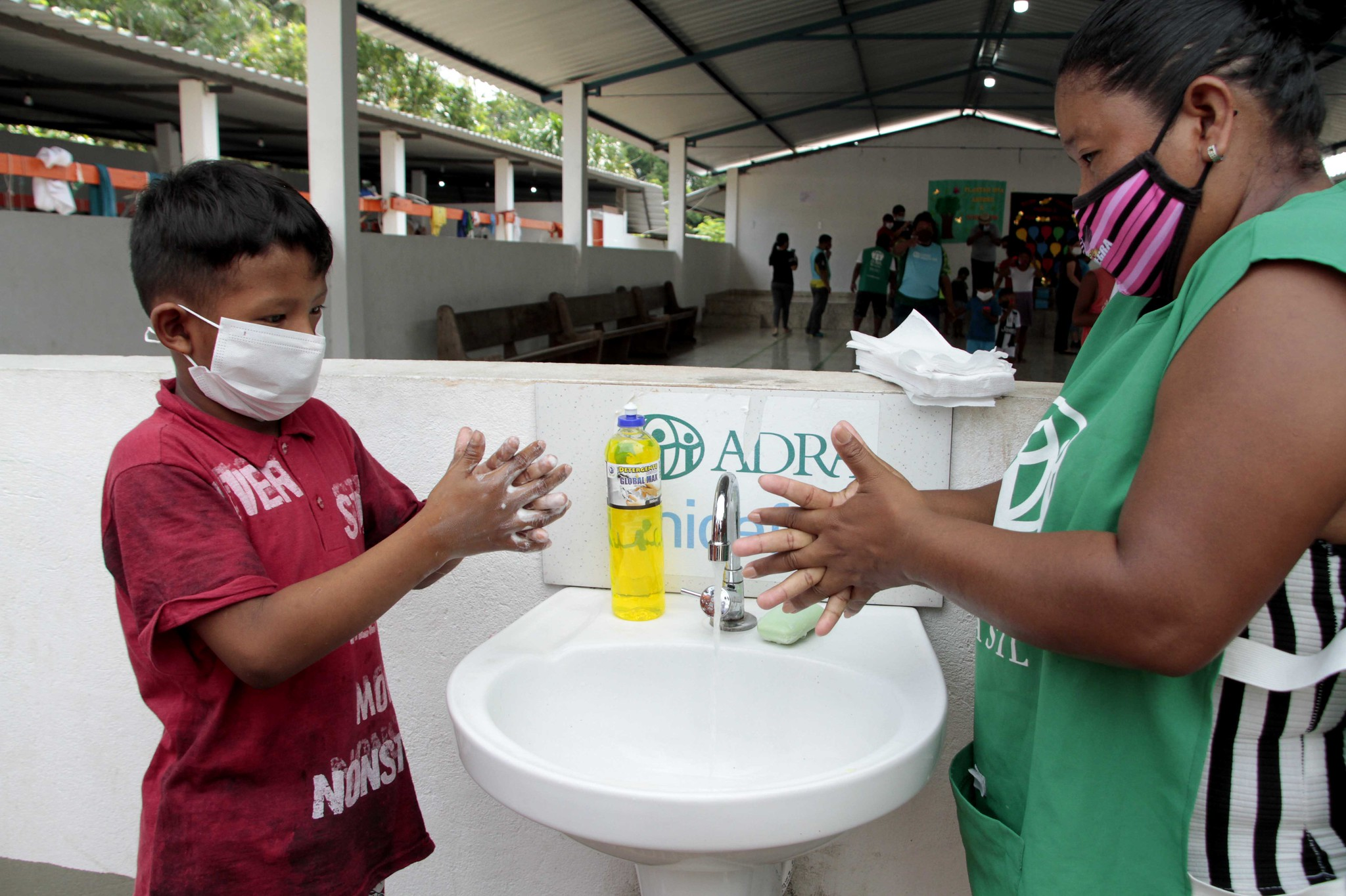 Mulher e criança lavam as mãos