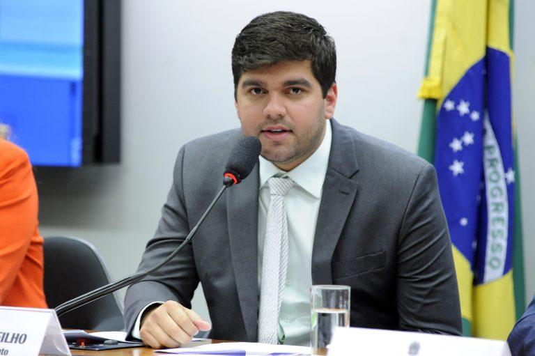 Deputado Marreca Filho está sentando falando ao microfone. Atrás dele há uma bandeira do Brasil