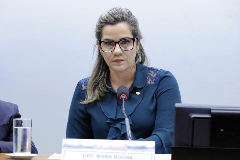 Deputada Mara Rocha está sentada e à frente dela há um microfone
