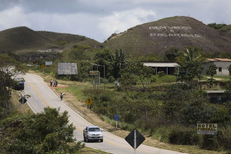 Uma rua passa por um povoado. Ao fundo há um morro escrito: Bem-vindos a Pacaraima