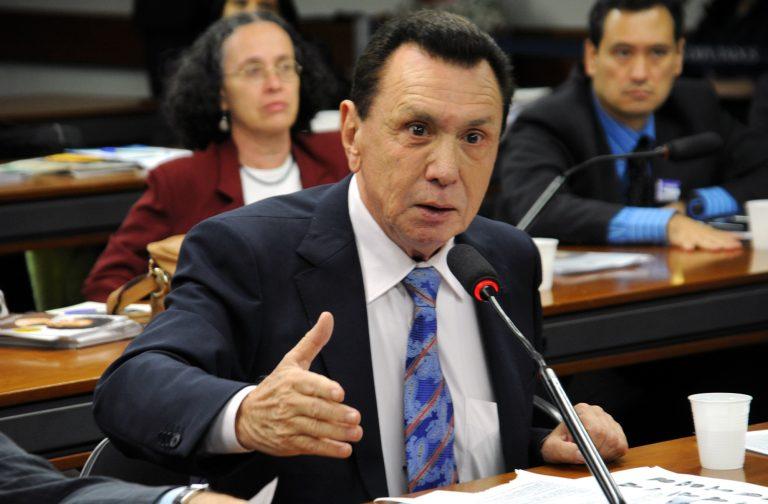 Deputado Carlos Bezerra está sentado falando ao microfone