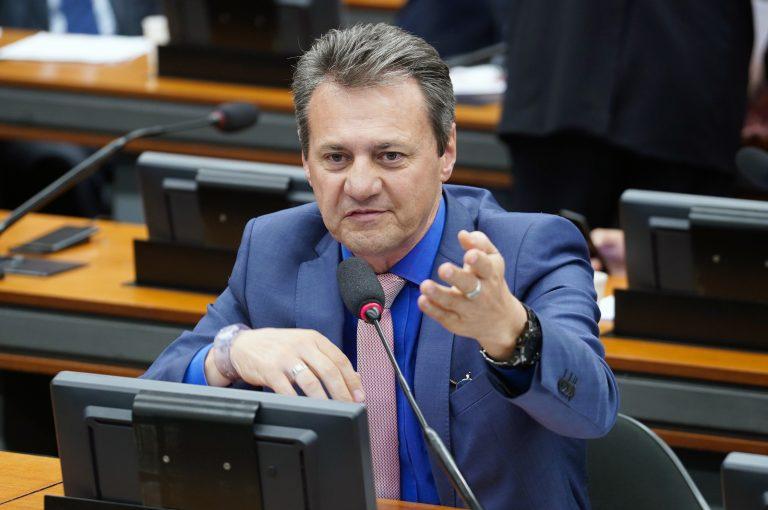 Deputado Giovani Cherini está sentado falando ao microfone