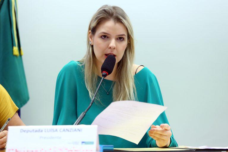 Deputada Luisa Canziani está sentada falando ao microfone