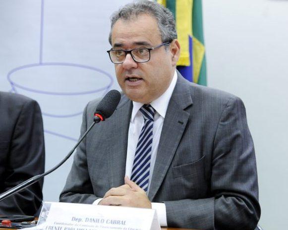 Deputado Danilo Cabral está sentado à mesa falando ao microfone