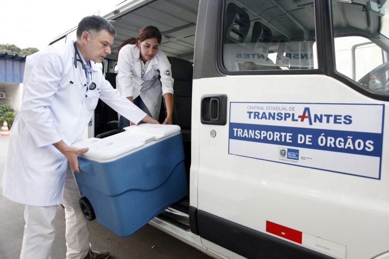 Duas pessoas carregam uma caixa térmica numa van da Central de Transplantes