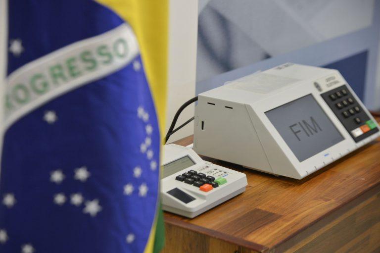 Uma urna eletrônica aparece em cima de uma mesa, junto à bandeira nacional