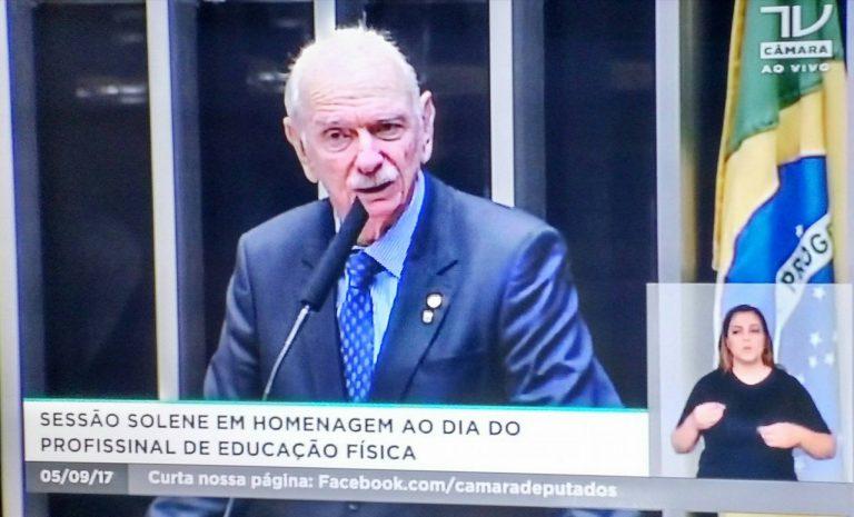 Imagem da TV Câmara com um parlamentar discursando e uma mulher fazendo a tradução em Libras