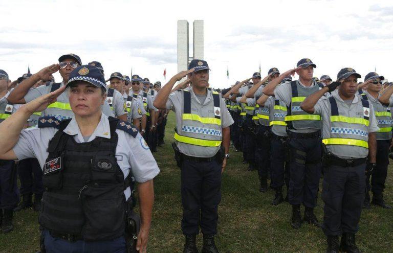 Policiais militares batem continência no gramado do Congresso Nacional