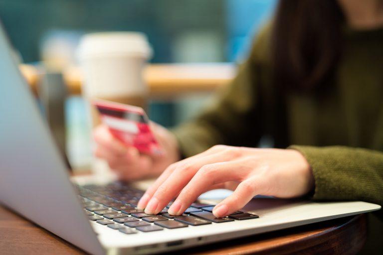 Mulher segura um cartão numa mão e digita no teclado com outra