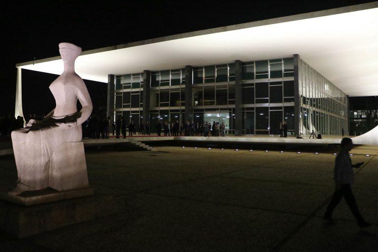 Estátua da Justiça e a fachada do prédio do Supremo Tribunal Federal à noite