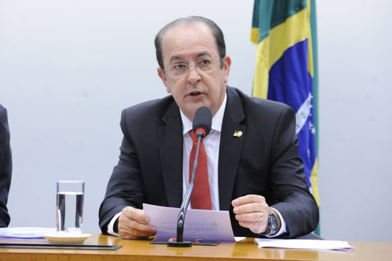 Deputado Luiz Carlos Motta está sentado à mesa e fala ao microfone