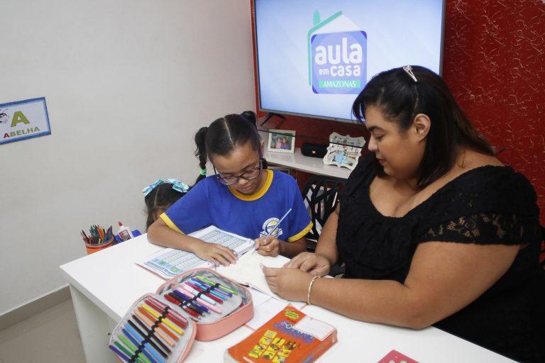 Sentada à mesa, mãe ajuda a filha a fazer as tarefas on-line da escola