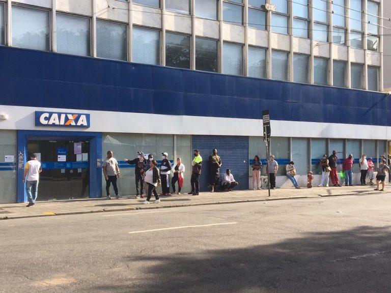 Pessoas fazem fila em frente a uma agência da Caixa Econômica para receber o auxílio emergencial