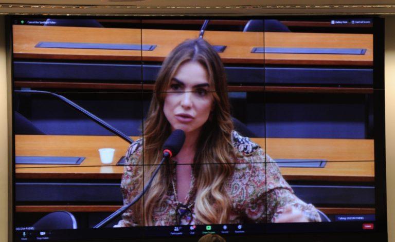 Deputada Paula Belmonte está sentada falando ao microfone