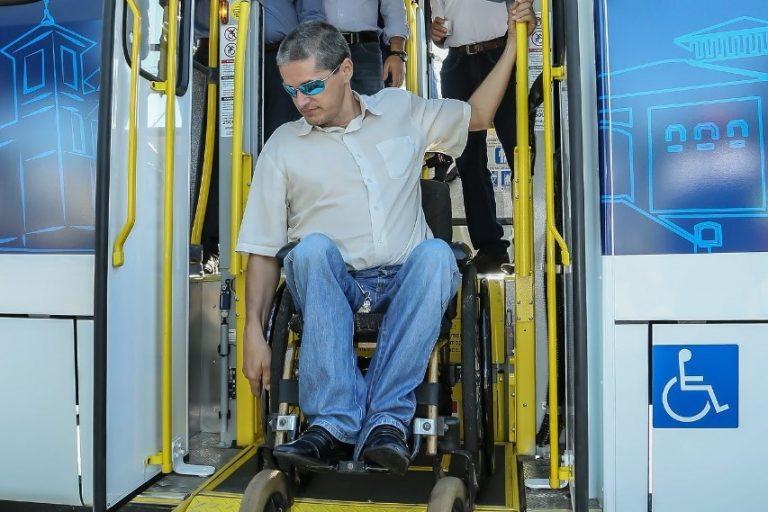 Homem na cadeira de rodas usa elevador para descer do ônibus