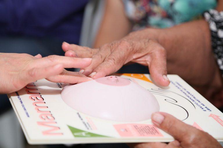 Mulher faz exame da mama numa prótese de plástico