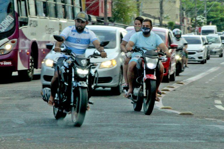 Carros e motos trafegam numa rua movimentada