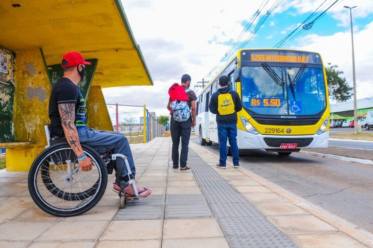 Homem em cadeira de rodas em ponto de ônibus com calçada com sinalização para cegos no piso