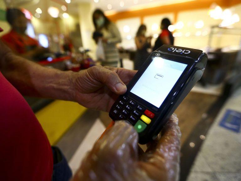 Comerciante segura uma maquininha de pagamento com cartão de crédito