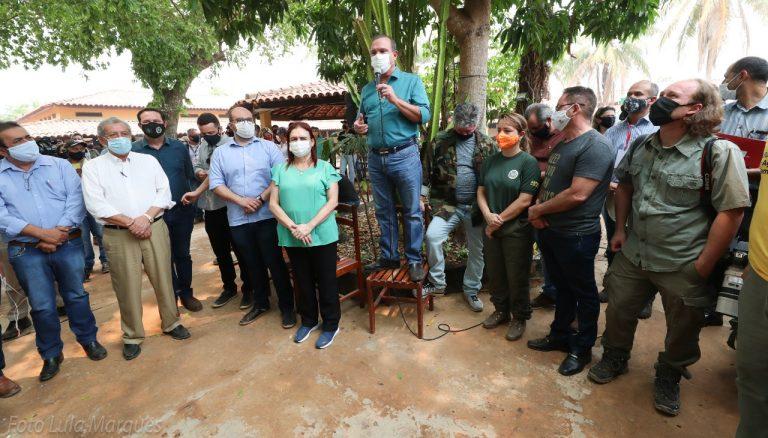 Um grupo de deputados está reunido numa área próxima a queimadas no Pantanal ouvindo uma pessoa discursar