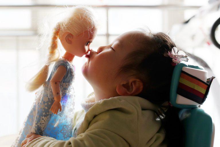 Menina com doença rara está sentada na cadeira de rodas e beija uma boneca