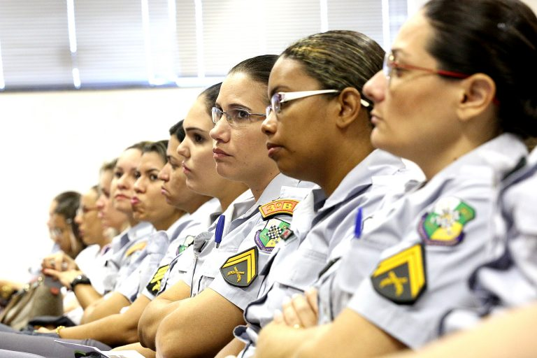 Várias mulheres policiais estão sentadas com os braços cruzados