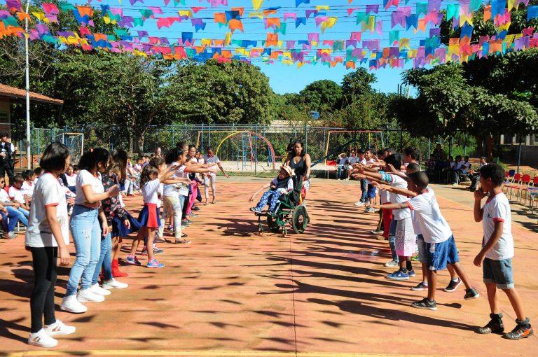 Criança numa cadeira de rodas participa de atividade escolar numa quadra de esportes