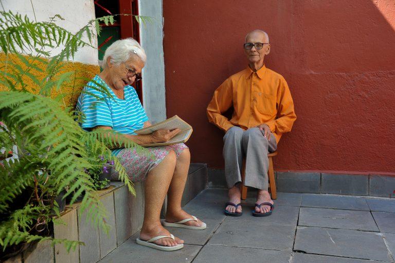 Casal de idosos está sentado. Ela lê e ele observa.