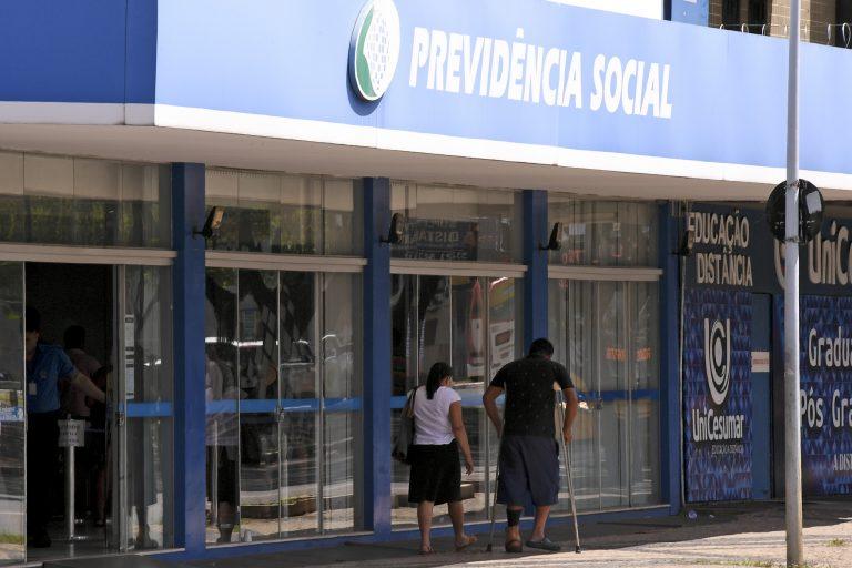 Homem de muleta em frente a agência da Previdência Social