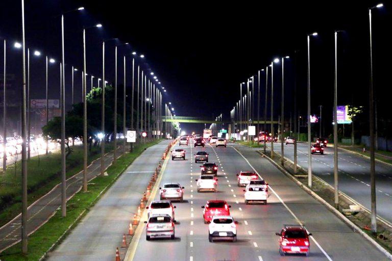 Carros trafegam em avenida à noite