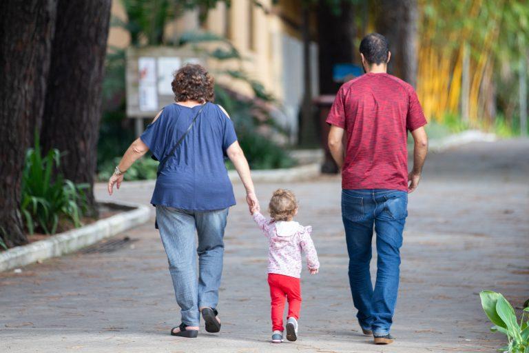 Um casal caminha segurando uma criança pequena pela mão