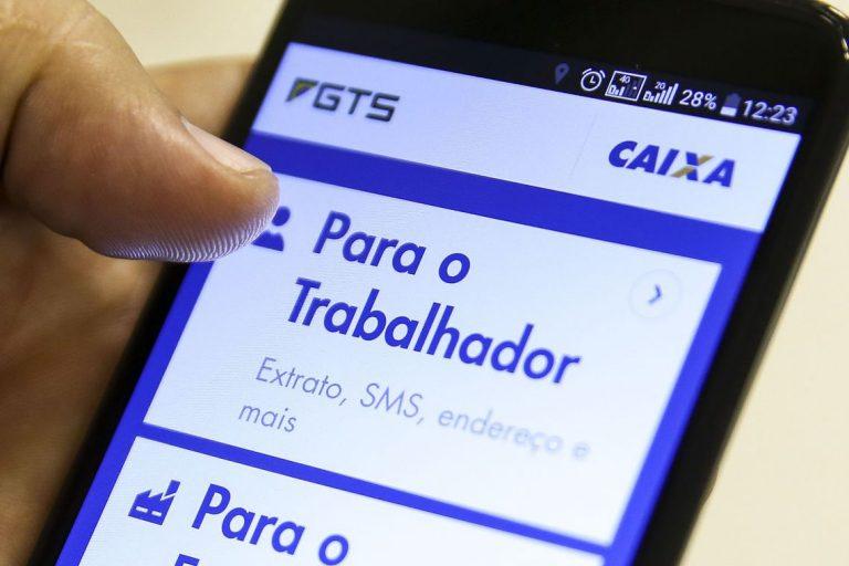 Mão segura celular mostrando aplicativo da Caixa para saque do FGTS
