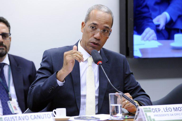 Deputado Léo Motta está sentado falando ao microfone
