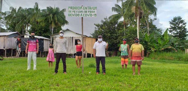 Índios estão em pé em frente a suas casas. Atrás há um cartaz onde se lê: Proibida entrada de pessoas de fora devido à Covid-19