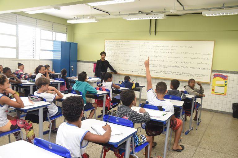 Sala de aula com crianças sentadas nas carteiras e a professora em pé ao lado do quadro