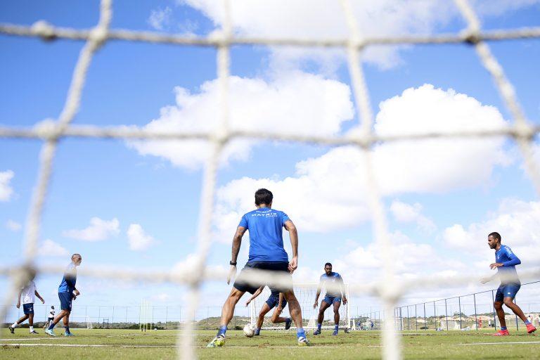 Homens jogam futebol num campo de grama