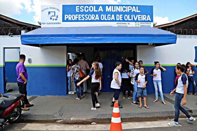 Fachada de uma escola municipal. Alguns alunos estão na calçada em frente à escola.