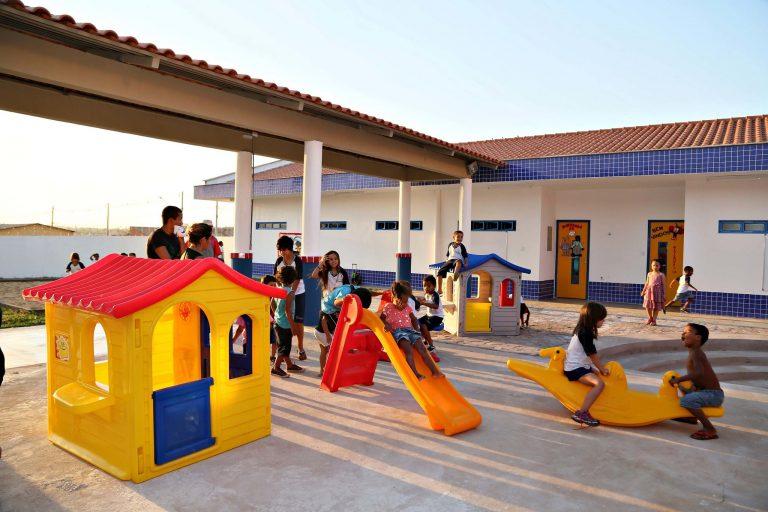 Pátio de escola infantil onde crianças brincam no parquinho