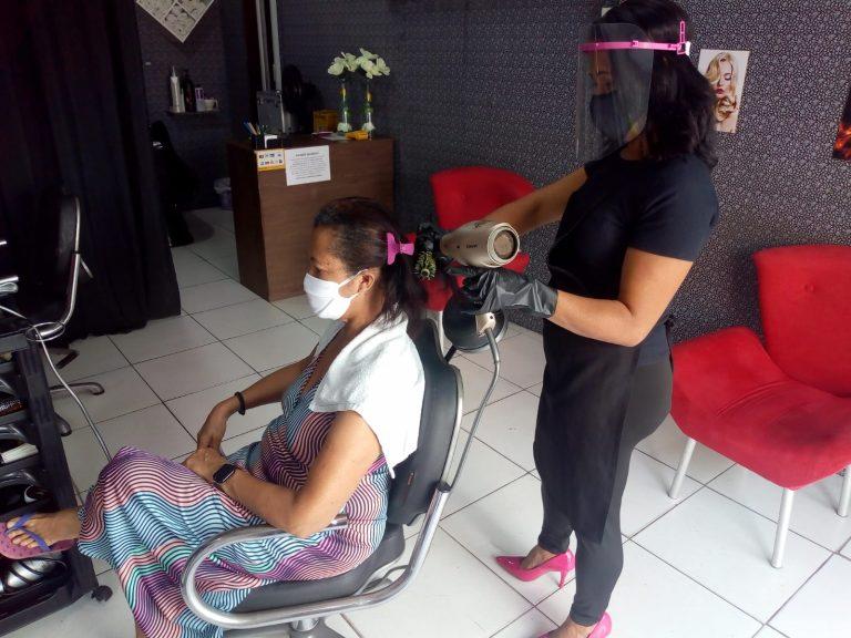 Cabelereira faz escova numa cliente. Ambas estão de máscaras contra a Covid-19