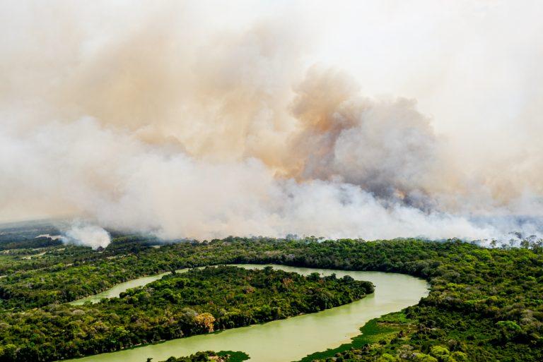 Rio no pantanal com incêndio ao fundo