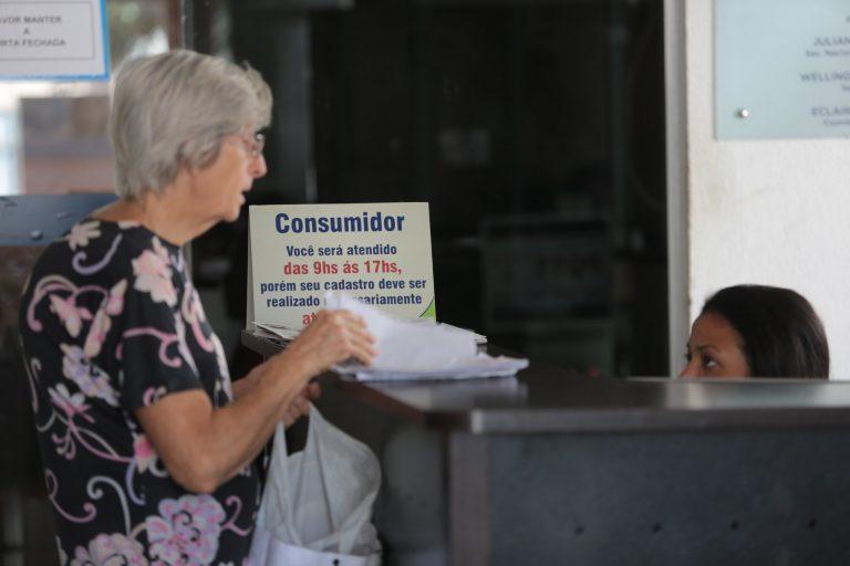 Idoso está em pé falando com uma funcionária num balcão de atendimento ao consumidor