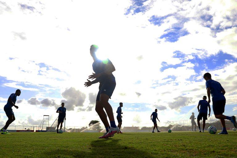 Jogadores de futebol fazem exercícios num campo de grama
