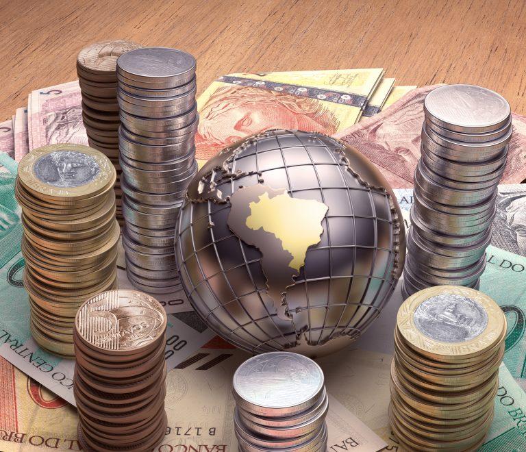 Moedas e cédulas de dinheiro estão em volta de um globo terrestre onde se destaca o Brasil