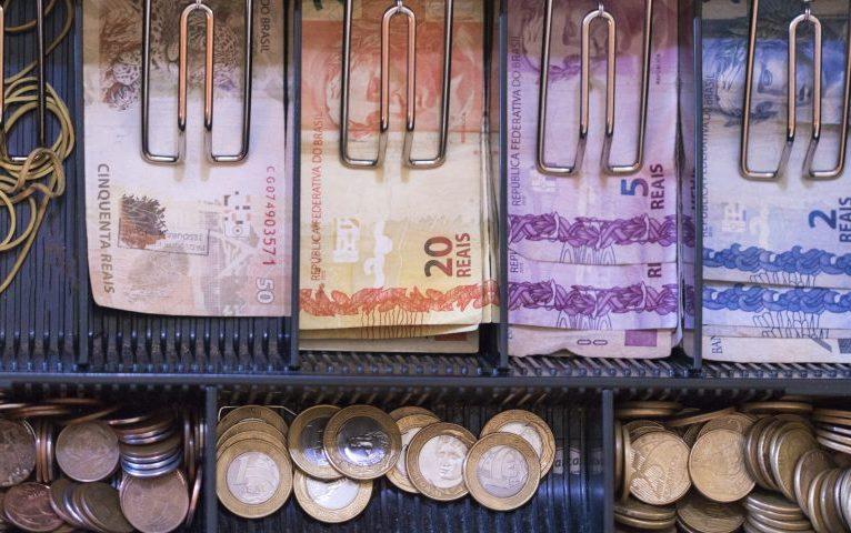 Caixa registradora com cedulas e moedas
