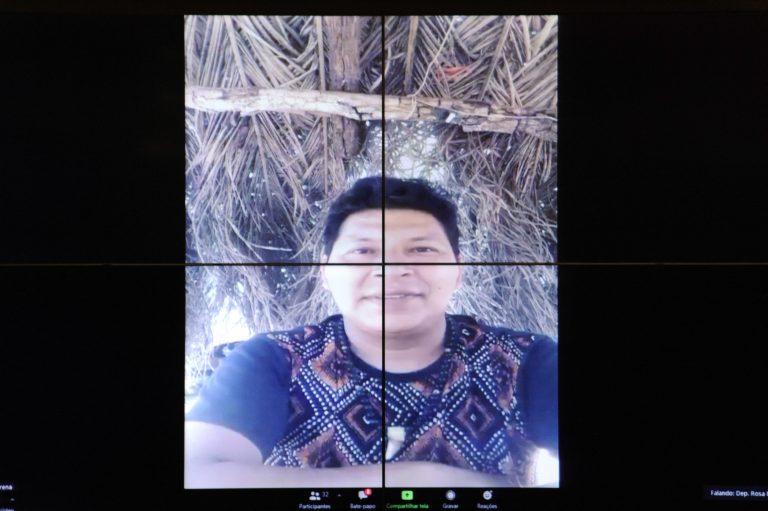 Índio da etnia Terena participa de videoconferência, em cima dele se vê um teto de palha