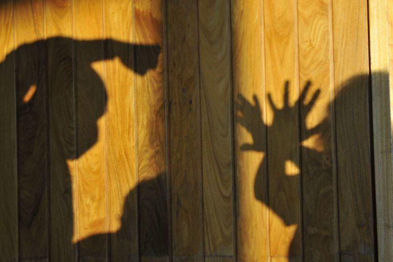 Sombra de um homem batendo numa mulher